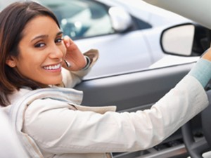 Portrait of a happy hispanic woman talking on mobile phone in car